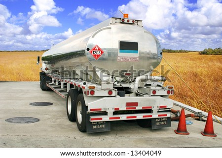 Tanker truck fueling an underground storage tank [isolated, names removed]. - stock photo