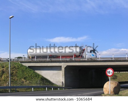 Tanker truck on the road crossing a bridge - stock photo