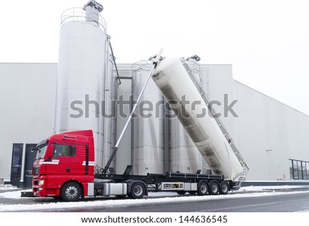 tanker truck refilling some large silos for food industry - stock photo