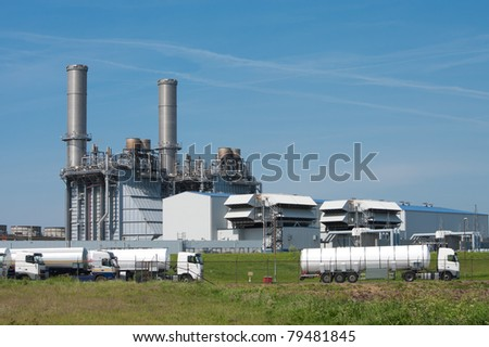 tanker trucks waiting to get loaded with fuel at an oil refinery - stock photo