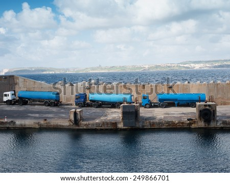 Tankers lined up on a cement wharf or dock on a pier at the side of a harbor waiting to refuel a ship or offload cargo - stock photo