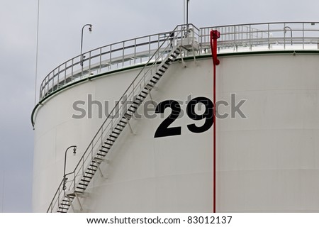 tanks in oil refinery factory on the cloudy sky - stock photo