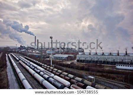 Tanks on train foreground and refinery complex - stock photo