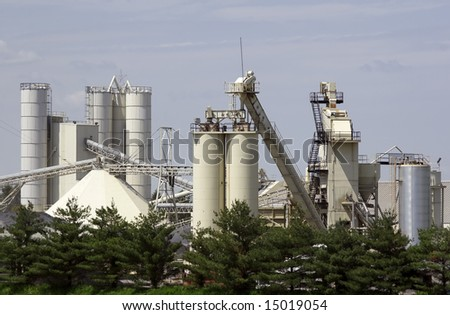 Tanks, silos, and conveyor at a stone quarry. - stock photo