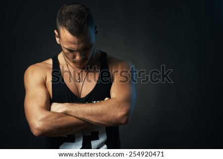 tanned athletic man on black background with his arms crossed - stock photo