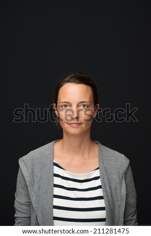 Tanned attractive young woman in a striped shirt and pullover standing looking at the camera with a serious expression over a dark background with copyspace - stock photo