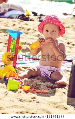 tanned baby playing on the beach in backlit - stock photo