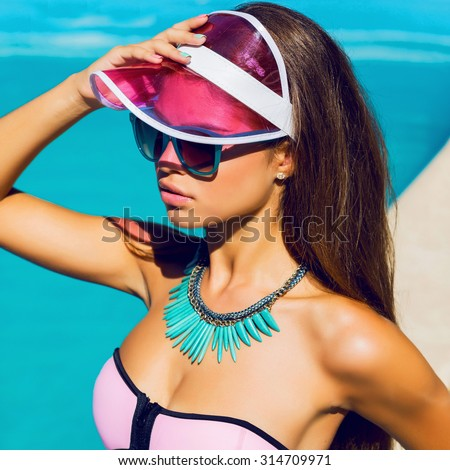 Tanned beautiful young model in pink stylish  beach  clothes and  bright color accessories sitting near swimming pool. Fashionable portrait. Sexy woman enjoying   summer in paradise  apartments. - stock photo