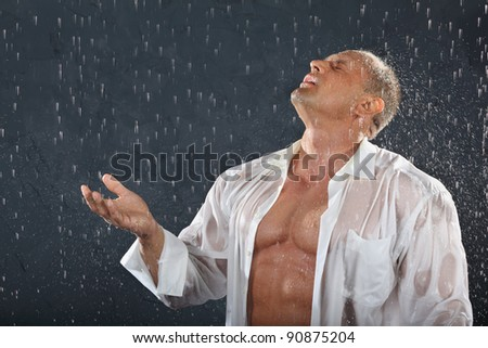 Tanned bodybuilder wearing white wet shirt stands in rain and catches drops by hand and mouth. - stock photo