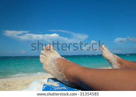 Tanned feet partially covered in sand on beach - stock photo