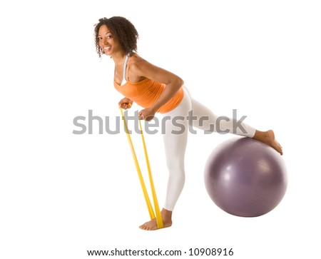 Tanned female performing stretching exercises using resistance bands and sport ball - stock photo