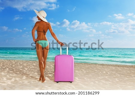 Tanned girl with big pink suitcase on beach - stock photo