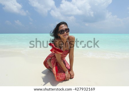 Tanned girl with dark hair in red pareo is sitting in the white Maldivian beach - stock photo