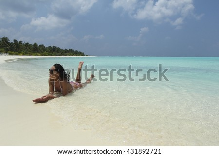 Tanned girl with dark hair lying in the maldivian beach - stock photo