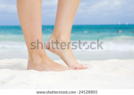 tanned legs of woman standing on the beach