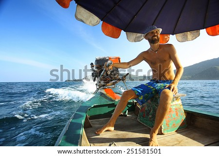 tanned man on the boat thailand vacation - stock photo