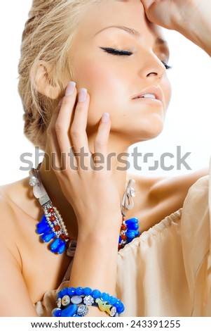 Tanned model posing in silk tunic and blue jewelery.
