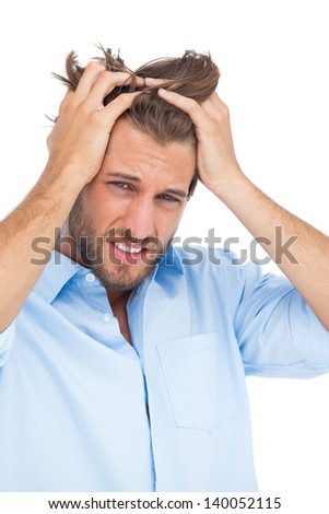 Tanned stressed man holding his hair on white background - stock photo