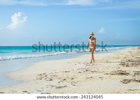 Tanned woman in white bikini enjoying idyllic tropical beach and caribbean summer vacation. Beautiful young tanned brunette enjoying a walk by the sea at Playa Paraiso, Riviera Maya, Mexico. - stock photo