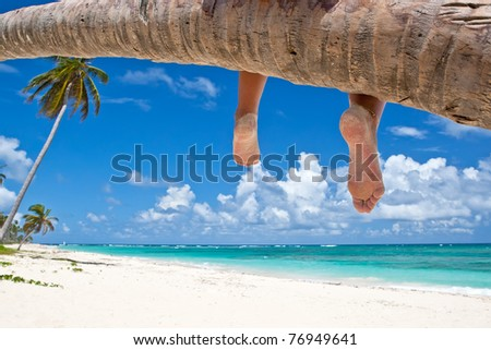 Tanned woman sitting on a palm white sand beach near ocean