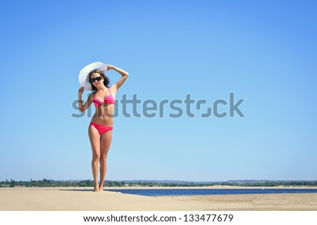 Tanned yound woman posing at the beach