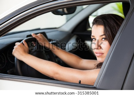 Tanned young driver looks at viewer though the side window of white car with dark interior