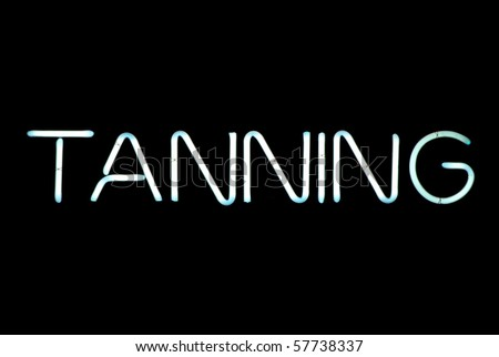 Tanning neon sign isolated on black background - stock photo