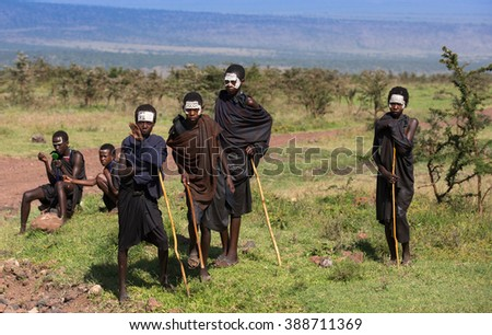 Tanzania 2016 Year February 15 . Masai boys in black clothes and painting faces on african savannah