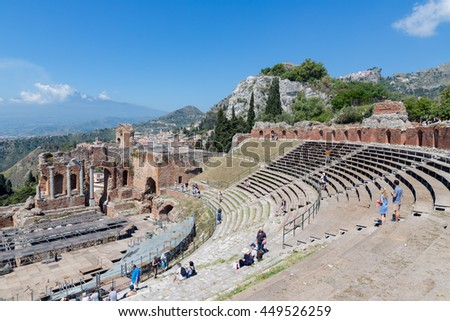 TAORMINA, ITALY - MAY 17: Tourists visiting ancient Greek theater of Taormina while workers mounting a stage and the Etna is visible at the horizon on May 17, 2016 in Taormina at the island Sicily