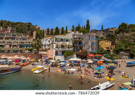 TAORMINA, SICILY - JUL 13, 2016; Relax on the beach in the picturesque Gulf of Mazzaro