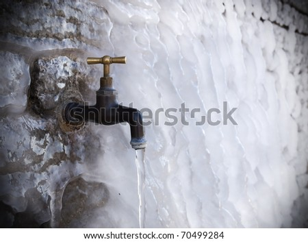 tap on frozen wall - stock photo
