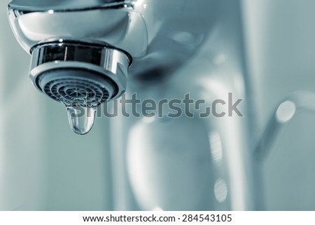 Tap with dripping waterdrop. Water leaking, saving. - stock photo