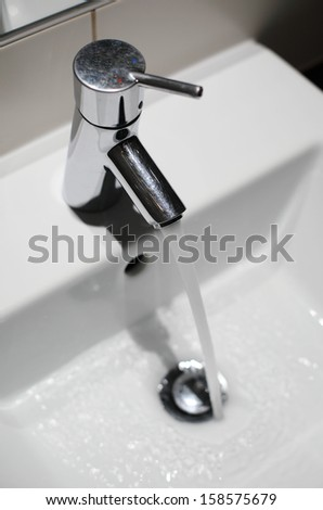 Tap with running water in bathroom - stock photo