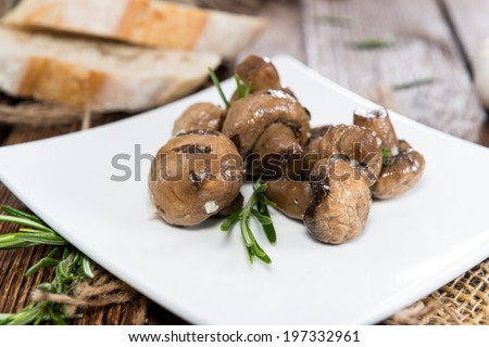 Tapas (Mushrooms) marinated with olive oil and some fresh herbs - stock photo