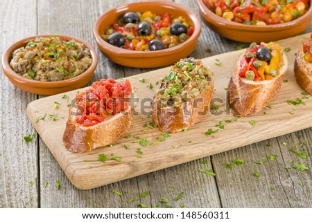Tapas on Crusty Bread - Selection of Spanish tapas served on a sliced baguette. Tomato spread, aubergine dip, roasted peppers and chorizo and chickpea toppings. - stock photo