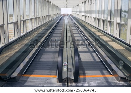 Tape escalator in glazed tunnel without people - stock photo