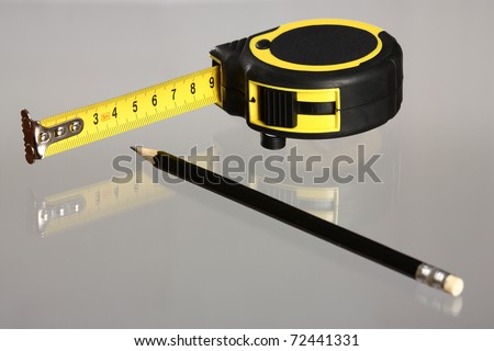 Tape measure and a pencil on neutral background with reflection - stock photo