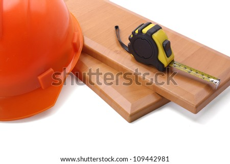 Tape measure and helmet, isolated on wooden background - stock photo
