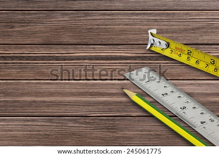 Tape measure and pencil on wooden background  - stock photo
