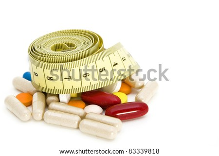 Tape measure and pills, weight loss concept - stock photo
