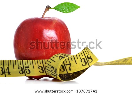 tape measure and red apple white background - stock photo