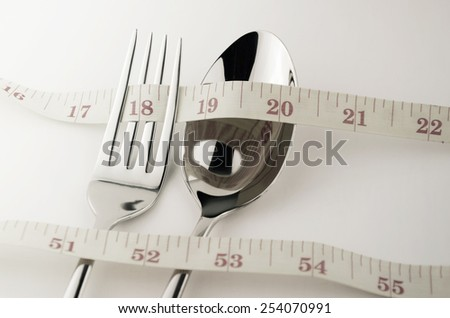 Tape Measure, Fork and Spoon in Waistline and Weight Control Concept by Diet Control. - stock photo