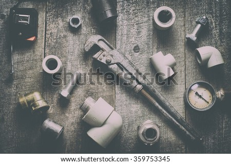 Tape-measure, internal screws, pipe screw, PVC pipe connectors, manometer on old wood table.  top view. copy space. - stock photo