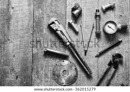 Tape-measure, internal screws, pipe wrench, bolts, manometer, diamond wheel on old wooden table. Copy space. black and white. - stock photo