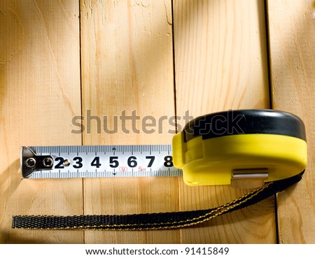 Tape measure on a wooden background - stock photo