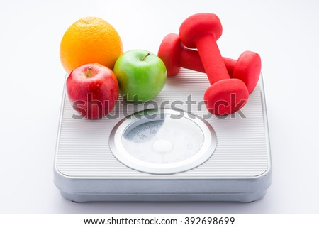 Tape measure on bathroom scale for weight of human body, dumbbells for fitness and fresh fruits. Concept of healthy lifestyle and slimming - stock photo