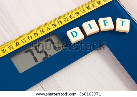 Tape measure on household digital bathroom scale for weight of human body, concept of healthy lifestyle and slimming - stock photo