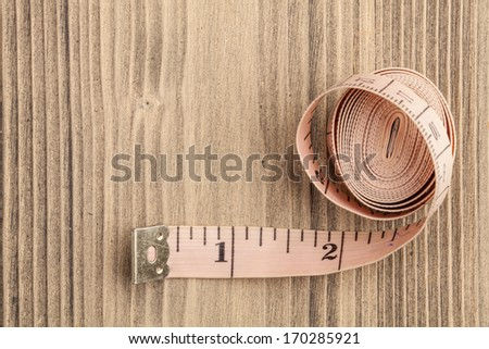 Tape measure on old wooden background. Top view. - stock photo
