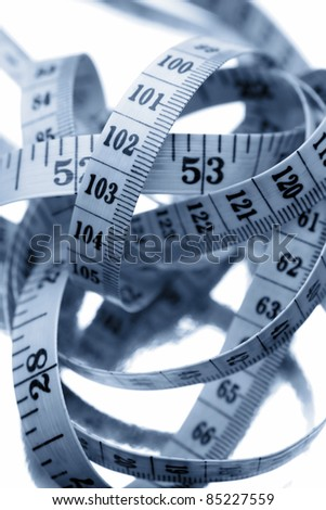 Tape measure on plain background - stock photo