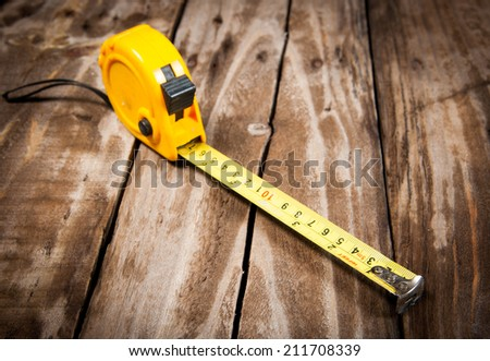 tape measure on the  wooden background - stock photo
